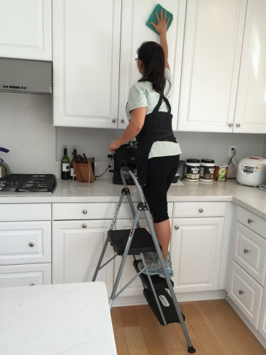 Photo of woman on ladder cleaning kitchen cabinet